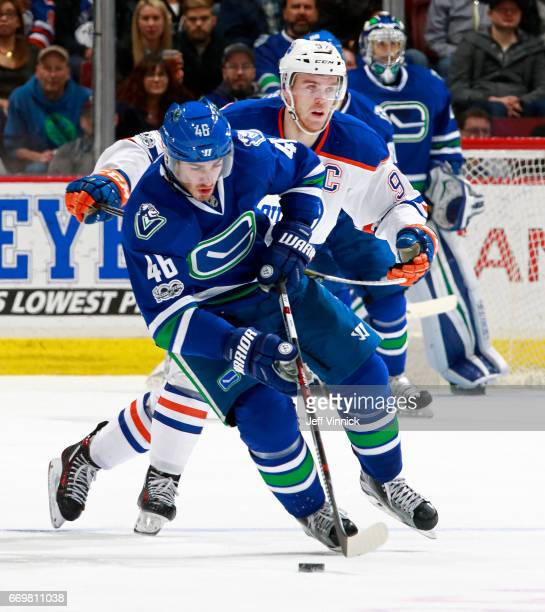 Leon Draisaitl of the Edmonton Oilers looks on as Jayson Megna of the Vancouver Canucks skates up ice with the puck during their NHL game at Rogers...