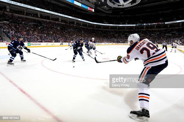 Leon Draisaitl of the Edmonton Oilers passes the puck across the ice as Jacob Trouba and Bryan Little of the Winnipeg Jets defend during third period...
