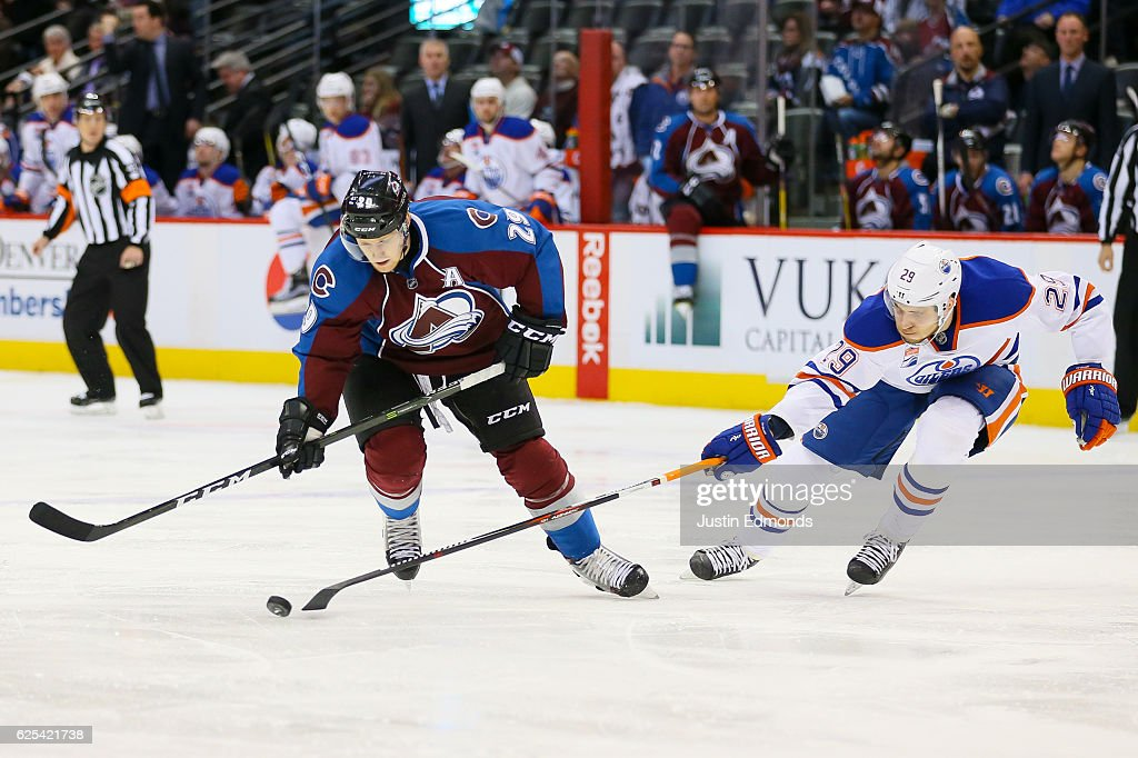 Leon Draisaitl #29 of the Edmonton Oilers pokes the puck away from Nathan MacKinnon #29 of the Colorado Avalanche during a power play in the second period at Pepsi Center on November 23, 2016 in Denver, Colorado.