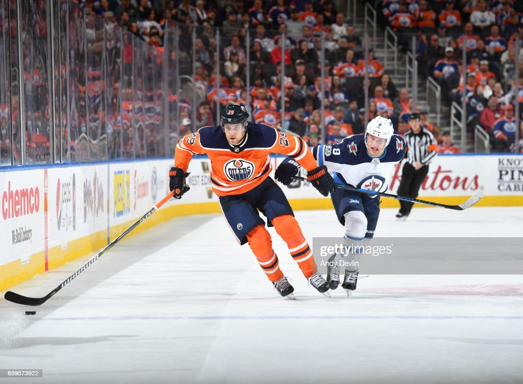 Leon Draisaitl #29 of the Edmonton Oilers skates with the puck while being pursued by Andrew Copp #9 of the Winnipeg Jets on October 9, 2017 at Rogers Place in Edmonton, Alberta, Canada.