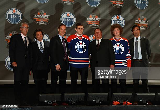 Leon Draisaitl poses on stage with team personnel after being selected third overall by the Edmonton Oilers during the 2014 NHL Entry Draft at Wells...