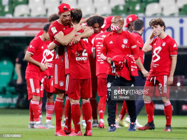 Leon Goretzka and Joshua Kimmich of FC Bayern Muenchen hug each other in celebration of winning the German Championship title after a 1-0 victory of...