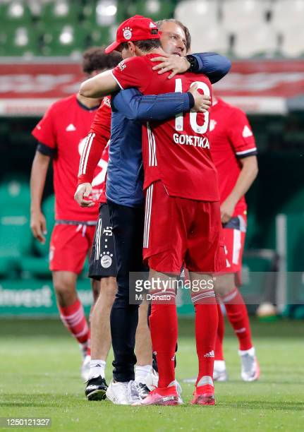 Leon Goretzka and team coach Hansi Flick of FC Bayern Muenchen hug each other in celebration of winning the German Championship title after a 10...