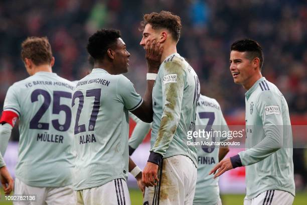 Leon Goretzka of Bayern Muenchen celebrates scoring his teams first goal of the game with team mates David Alaba during the Bundesliga match between...