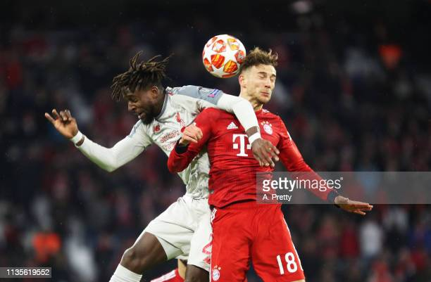 Leon Goretzka of Bayern Muenchen challenges Divock Origi of Liverpool during the UEFA Champions League Round of 16 Second Leg match between FC Bayern...