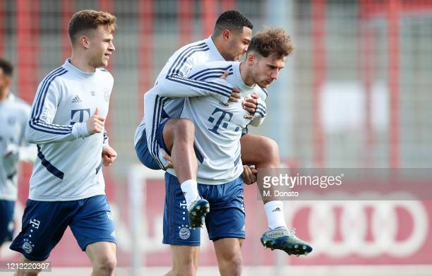 Leon Goretzka of FC Bayern Muenchen carries Serge Gnabry on his back next to Joshua Kimmich during a training session at Saebener Strasse training...