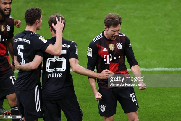 Leon Goretzka of FC Bayern Muenchen celebrates with teammate Benjamin Pavard and Thomas Mueller after scoring their team's first goal during the...