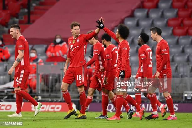 Leon Goretzka of FC Bayern Muenchen celebrates with teammate Leroy Sane after scoring their team's third goal during the Bundesliga match between FC...