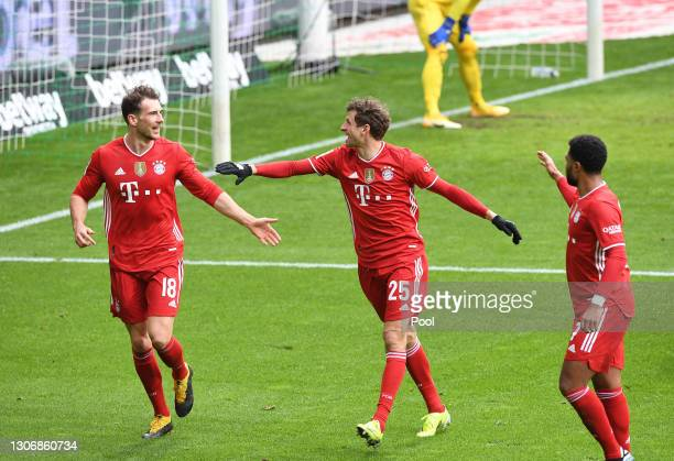 Leon Goretzka of FC Bayern Muenchen celebrates with teammates Thomas Mueller and Serge Gnabry after scoring his team's first goal during the...