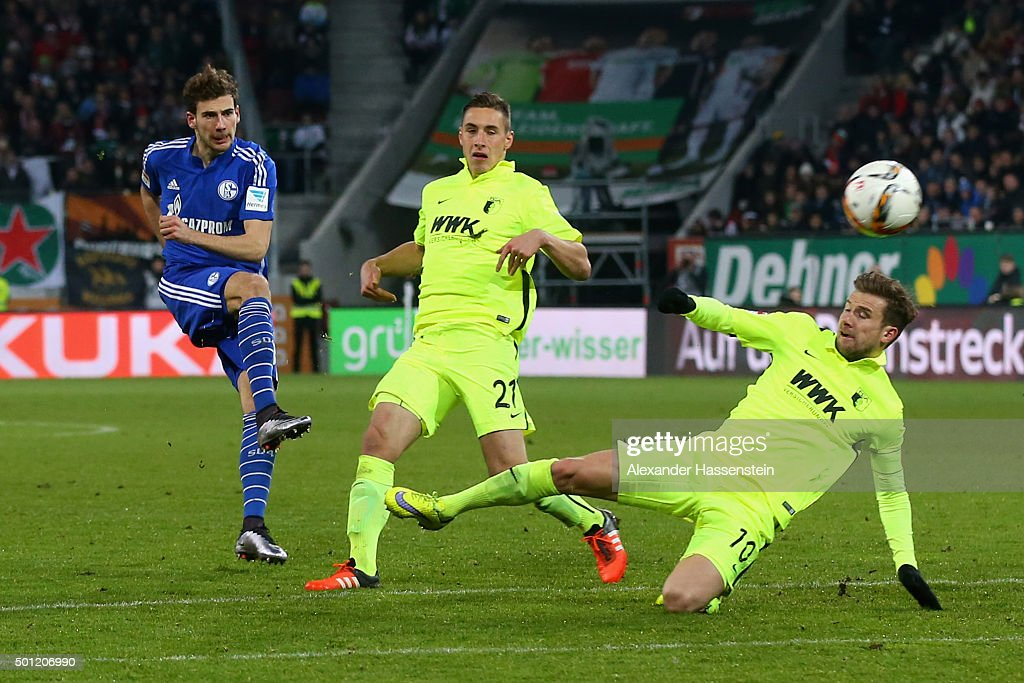 Leon Goretzka (L) of Schalke battles for the ball with Dominik Kohr (C) of Augsburg and his team mate Daniel Baier during the Bundesliga match between FC Augsburg and FC Schalke 04 at WWK Arena on December 13, 2015 in Augsburg, Germany.