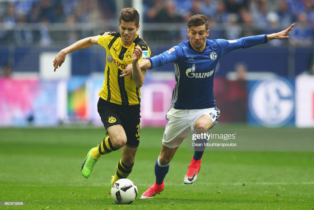 Leon Goretzka of Schalke battles for the ball with Dzenis Burnic of Borussia Dortmund during the Bundesliga match between FC Schalke 04 and Borussia Dortmund at Veltins-Arena on April 1, 2017 in Gelsenkirchen, Germany.