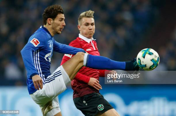 Leon Goretzka of Schalke is challenged by Felix Klaus of Hannover during the Bundesliga match between FC Schalke 04 and Hannover 96 at VeltinsArena...