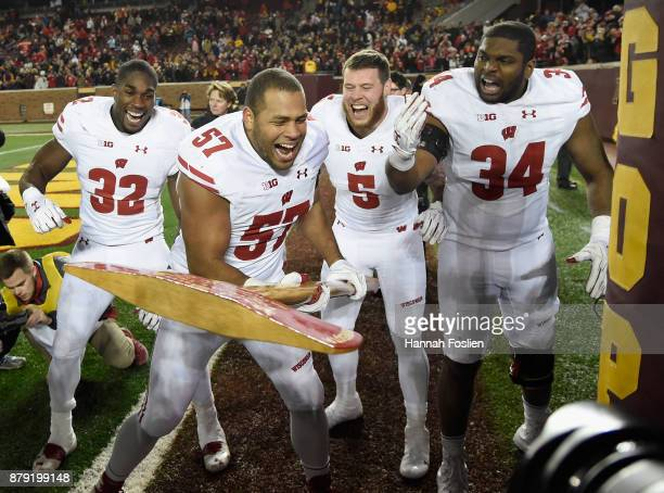Leon Jacobs Garret Dooley Chikwe Obasih of the Wisconsin Badgers cheer on teammate Alec James as he pretends to chop down the goal post with Paul...