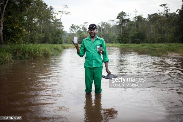 Leon Koli, ranger for WWF, stands in water as he poses for a picture with his smartphone in the Dzanga-Ndoki National Park, in Bayanga, in the...