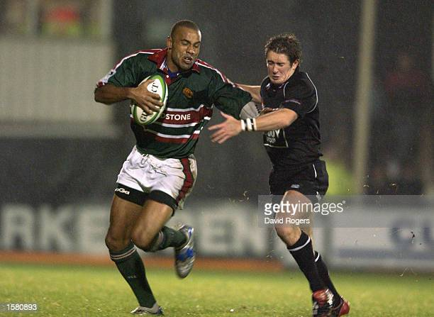Leon Lloyd of Leicester Tigers takes the ball past Shane Williams of Neath during the Heineken Cup Pool 1 match held on October 11 2002 at the Gnoll...