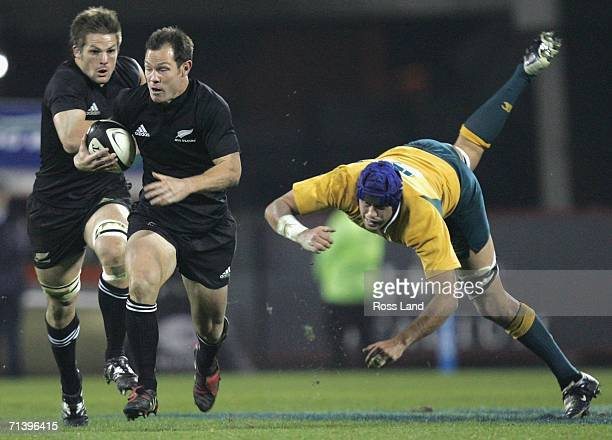 Leon MacDonald of the All Blacks leaves Nathan Sharpe of the Wallabies in his wake during the Tri Nations series Bledisloe Cup match between the New...