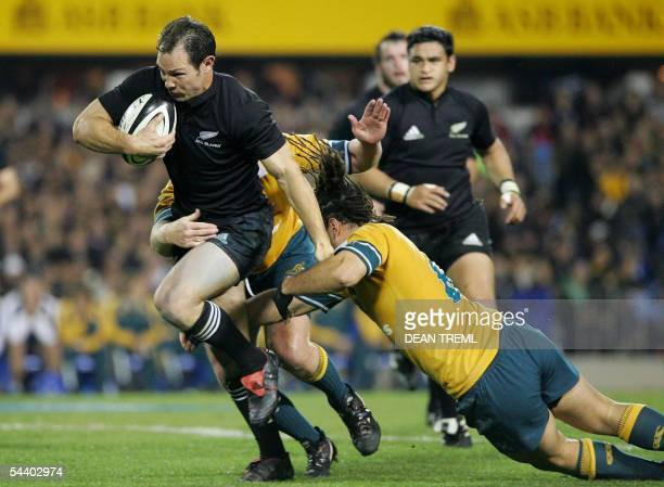 Leon MacDonald of the All Blacks tries to evade two Australian players during the Tri Nations rugby union test match between the New Zealand All...