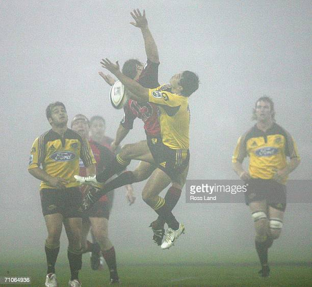 Leon MacDonald of the Crusaders and Tamati Ellison of the Hurricanes compete for high ball in heavy fog during the Super 14 final match between the...