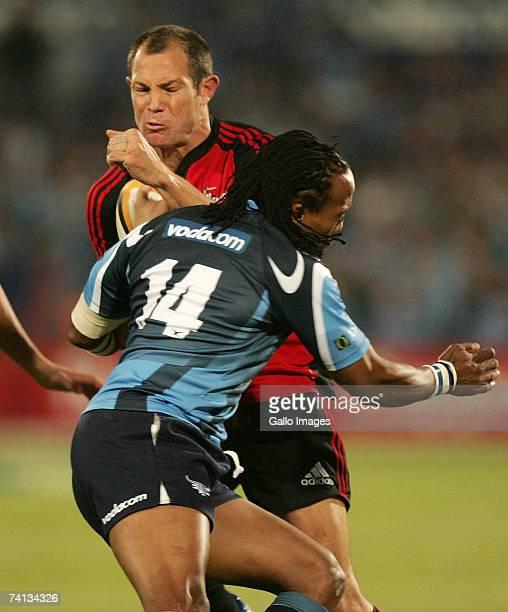 Leon MacDonald stopped by Akhona Ndungane during the Super 14 semifinal match between the Vodacom Bulls and the Crusaders held at the Loftus Versfeld...