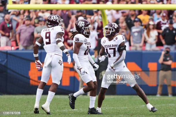 Leon O'Neal Jr. #9, Brian George and Jaylon Jones of the Texas A&M Aggies celebrate after making a defensive stop on fourth down against the Colorado...