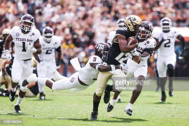 Leon O'Neal Jr. #9 of the Texas A&M Aggies attempts to tackle Brendon Lewis of the Colorado Buffaloes during the first quarter at Empower Field At...