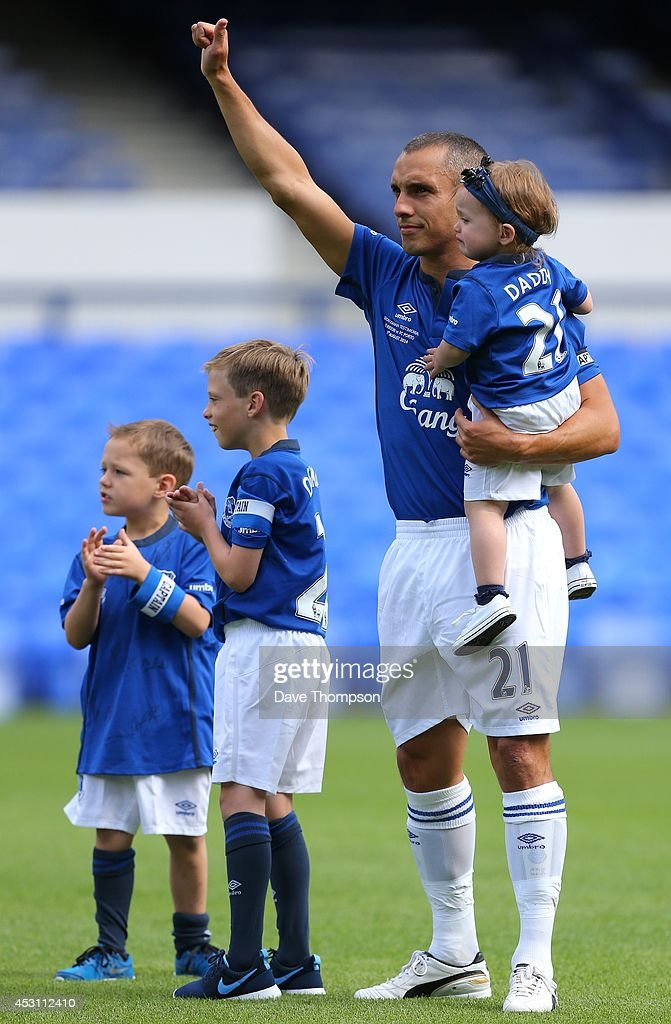 Leon Osman of Everton acknowledges the fans as he arrives on the pitch with his children for his testimonial match, the Pre-Season Friendly between Everton and Porto at Goodison Park on August 3, 2014 in Liverpool, England.