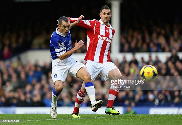 Leon Osman of Everton in action with Geoff Cameron of Stoke City during the Barclays Premier League match between Everton and Stoke City at Goodison...