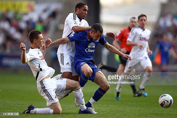 Leon Osman of Everton is tackled by Ashley Williams and Josh McEachran of Swansea during the Barclays Premier League match between Swansea City and...