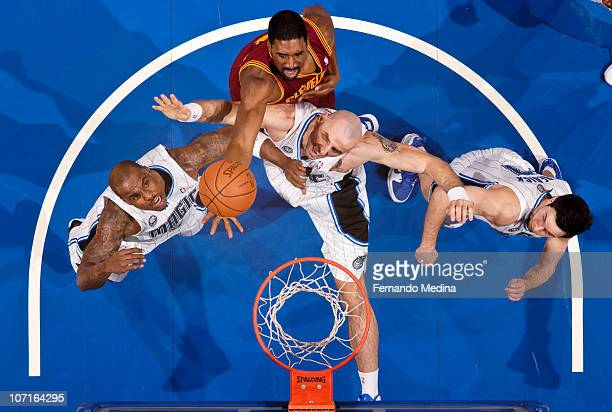 Leon Powe of the Cleveland Cavaliers reaches for a rebound over Marcin Gortat and Quentin Richardson of the Orlando Magic on November 26 2010 at the...