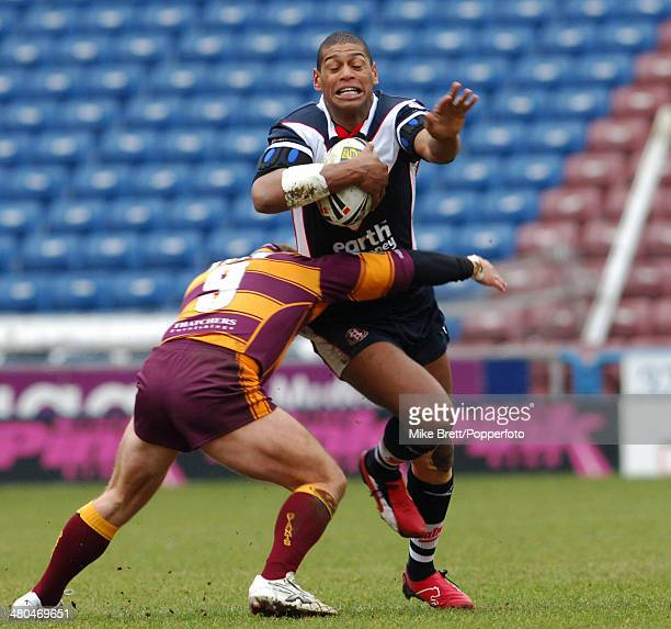Leon Pryce of St Helens tries to evade the tackle of Huddersfield Giants Brad Drew during their Rugby Super League match held at Galpharm Stadium...