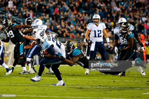 Leon Washington of the Tennessee Titans is tackled by Craig Loston of the Jacksonville Jaguars in the fourth quarter at EverBank Field on December 18...