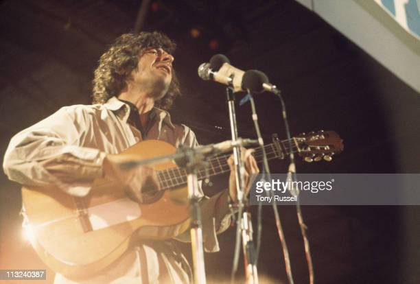 Leonard Cohen Canadian singersongwriter musician and poet playing the guitar and singing into a microphone during a live concert performance at the...