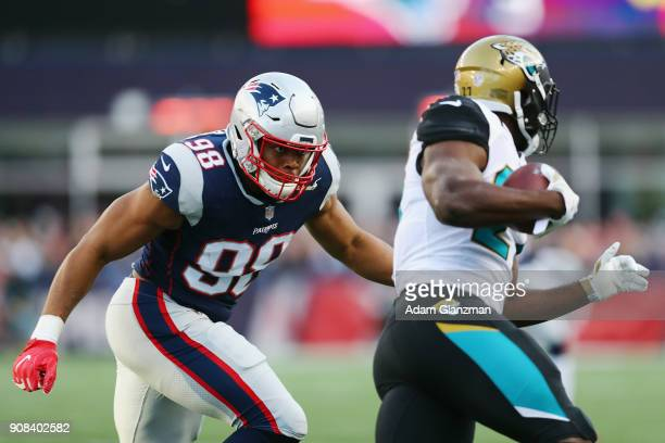 Leonard Fournette of the Jacksonville Jaguars carries the ball as he is defended by Trey Flowers of the New England Patriots in the first quarter...