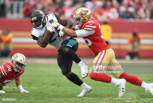 Leonard Fournette of the Jacksonville Jaguars gets tackled by Brock Coyle of the San Francisco 49ers during their NFL football game at Levi's Stadium...