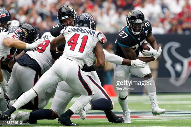 Leonard Fournette of the Jacksonville Jaguars runs the ball defended by Zach Cunningham of the Houston Texans in the second half at NRG Stadium on...