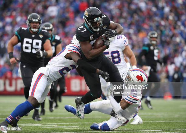 Leonard Fournette of the Jacksonville Jaguars runs with the ball in the second quarter as he is tackled by TreDavious White of the Buffalo Bills and...