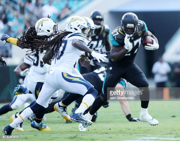 Leonard Fournette of the Jacksonville Jaguars runs with the football against Jahleel Addae of the Los Angeles Chargers in the first half of their...