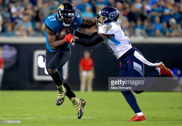 Leonard Fournette of the Jacksonville Jaguars rushes against Kevin Byard of the Tennessee Titans during a game at TIAA Bank Field on September 19...