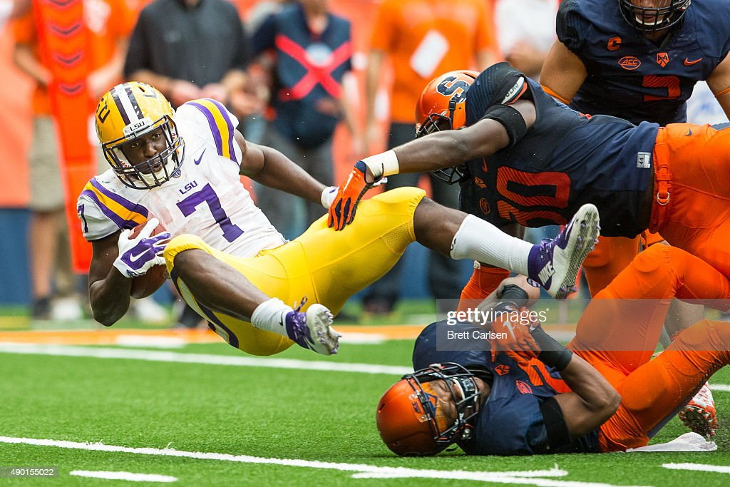 Leonard Fournette #7 of the LSU Tigers flies through the air after being tackled by Chauncey Scissum #21 of the Syracuse Orange on September 26, 2015 at The Carrier Dome in Syracuse, New York. LSU defeats Syracuse 34-24.