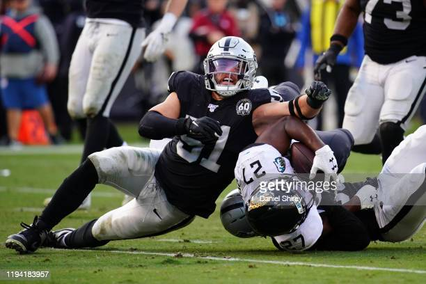 Leonard Fournette of the Oakland Raiders is tackled by Will Compton of the Oakland Raiders during the second half at RingCentral Coliseum on December...