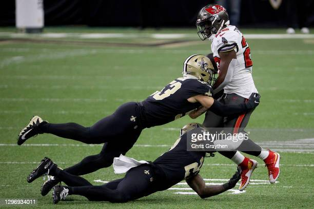 Leonard Fournette of the Tampa Bay Buccaneers gets tackled by Zack Baun and Malcolm Jenkins of the New Orleans Saints in the NFC Divisional Playoff...