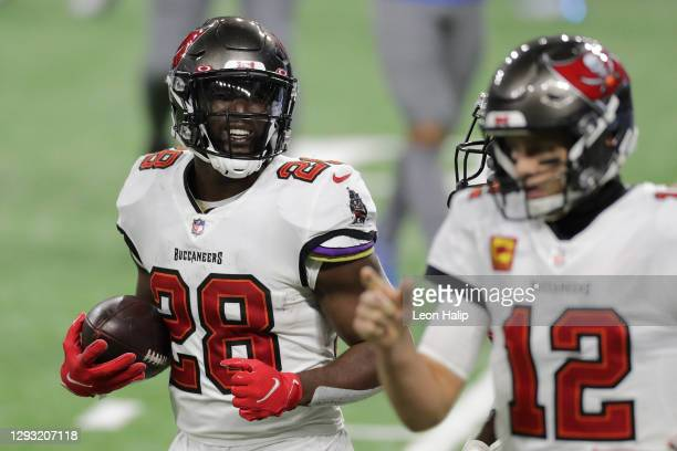 Leonard Fournette of the Tampa Bay Buccaneers walks off the field following a touchdown alongside Tom Brady during the second quarter of a game...