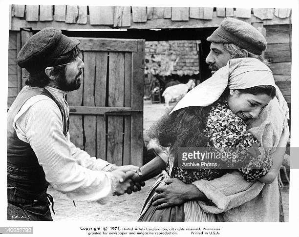 Leonard Frey shaking hand of Topol while Norma Crane hugs him in a scene from the film 'Fiddler On The Roof' 1971