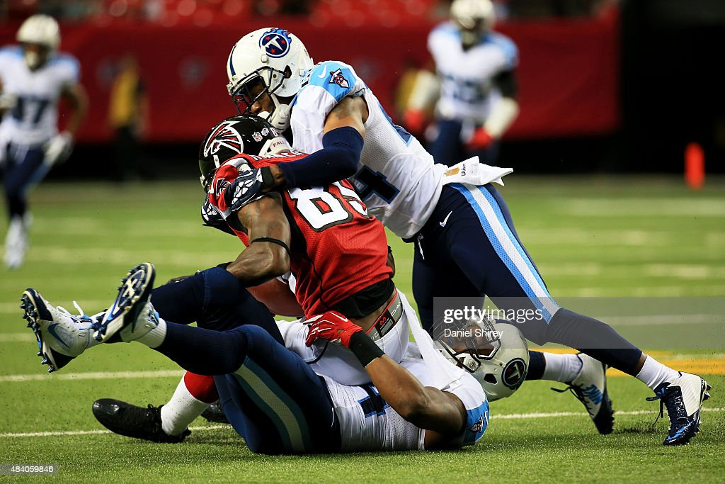 Leonard Hankerson #85 of the Atlanta Falcons is tackled by Coty Sensabaugh #24 and Avery Williamson #54 of the Tennessee Titans in the first half of a preseason game at the Georgia Dome on August 14, 2015 in Atlanta, Georgia.