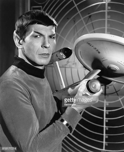 Leonard Nimoy as the logical Vulcan Mr Spock first officer on the Starship Enterprise a model of which he holds