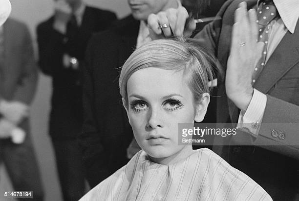 Leonard of London cuts model Twiggy's hair during a press conference announcing her television special.