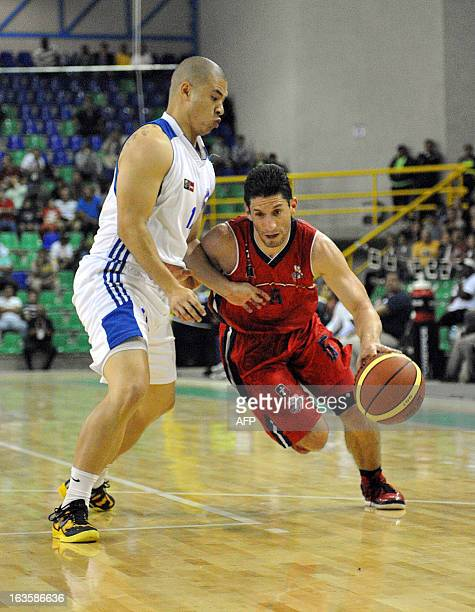 Leonardo Amador of Honduras and Costa Rican Cristian Chavarria play during their basketball match during the 10th Central American Games in San Jose...