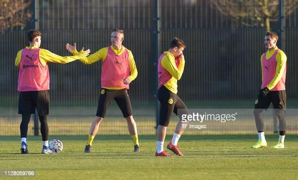Leonardo Balerdi of Borussia Dortmund gives a highfive to Marius Wolf of Borussia Dortmund while Raphael Guerreiro of Borussia Dortmund gestures and...