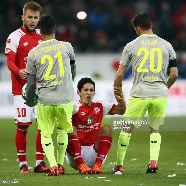 Leonardo Bittencourt and Salih Oeczan of Koeln help up Yoshinori Muto of Mainz during the Bundesliga match between 1 FSV Mainz 05 and 1 FC Koeln at...