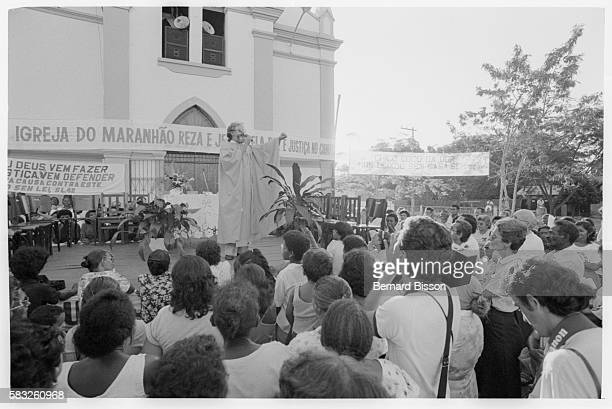 Leonardo Boff preaches from a raised platform outside a church to a crowd of followers of Liberation Theology The promotion of direct social action...